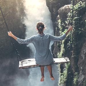 Junge Frau auf Schaukel über Wasserfall